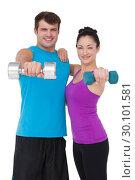 Купить «Fit man and woman lifting dumbbells», фото № 30101581, снято 13 ноября 2014 г. (c) Wavebreak Media / Фотобанк Лори