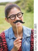 Купить «Pretty brunette with fake mustache», фото № 30101881, снято 11 ноября 2014 г. (c) Wavebreak Media / Фотобанк Лори