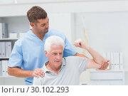 Купить «Physiotherapist giving physical therapy to man», фото № 30102293, снято 13 ноября 2014 г. (c) Wavebreak Media / Фотобанк Лори