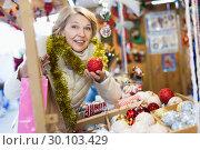 Купить «Smiling woman choosing Christmas toys at Christmas market», фото № 30103429, снято 21 декабря 2017 г. (c) Яков Филимонов / Фотобанк Лори
