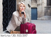 Купить «Adult woman 50s years old is sitting with suitcase», фото № 30103597, снято 3 сентября 2017 г. (c) Яков Филимонов / Фотобанк Лори