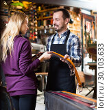 Купить «Smiling male worker assisting female customer in choosing belt», фото № 30103633, снято 26 июня 2019 г. (c) Яков Филимонов / Фотобанк Лори