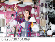 Купить «girl in lighter shop choosing modern glass chandelier for house interior», фото № 30104069, снято 16 февраля 2017 г. (c) Яков Филимонов / Фотобанк Лори