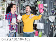 Купить «Male 28-37 and female 18-24 years old in shop of home appliances are choosing night lamp», фото № 30104105, снято 16 февраля 2017 г. (c) Яков Филимонов / Фотобанк Лори