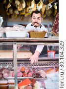 Купить «Male shop assistant demonstrating sliced bacon in butcher's shop», фото № 30104329, снято 2 января 2017 г. (c) Яков Филимонов / Фотобанк Лори