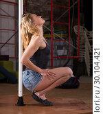 Купить «Young woman in denim shorts practicing pole dancing», фото № 30104421, снято 22 апреля 2019 г. (c) Яков Филимонов / Фотобанк Лори