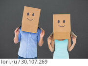 Composite image of couple wearing emoticon face boxes on their heads. Стоковое фото, агентство Wavebreak Media / Фотобанк Лори