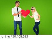 Купить «Composite image of cool young couple holding red heart», фото № 30108593, снято 21 января 2015 г. (c) Wavebreak Media / Фотобанк Лори