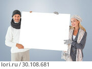 Composite image of smiling couple in winter fashion holding poster. Стоковое фото, агентство Wavebreak Media / Фотобанк Лори