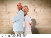 Composite image of smiling couple standing leaning backs together. Стоковое фото, агентство Wavebreak Media / Фотобанк Лори