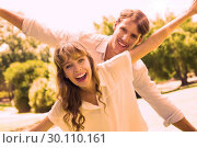 Купить «Attractive couple smiling at camera and spreading arms in the park», фото № 30110161, снято 31 января 2014 г. (c) Wavebreak Media / Фотобанк Лори