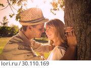 Купить «Cute smiling couple leaning against tree in the park», фото № 30110169, снято 31 января 2014 г. (c) Wavebreak Media / Фотобанк Лори