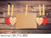 Купить «Composite image of hearts hanging on line with card», фото № 30111489, снято 23 января 2015 г. (c) Wavebreak Media / Фотобанк Лори