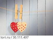 Купить «Composite image of hearts hanging on the line», фото № 30111497, снято 23 января 2015 г. (c) Wavebreak Media / Фотобанк Лори