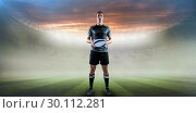 Composite image of serious rugby player in black jersey holding ball. Стоковое фото, агентство Wavebreak Media / Фотобанк Лори