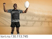 Купить «Composite image of cheerful sportsman with clenched fist holding rugby ball», фото № 30113745, снято 17 сентября 2015 г. (c) Wavebreak Media / Фотобанк Лори