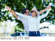 Купить «Couple with arms outstretched against trees», фото № 30117181, снято 3 февраля 2016 г. (c) Wavebreak Media / Фотобанк Лори