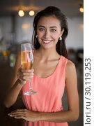 Portrait of smiling woman holding a champagne flute. Стоковое фото, агентство Wavebreak Media / Фотобанк Лори