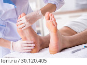 Купить «Podiatrist treating feet during procedure», фото № 30120405, снято 29 августа 2018 г. (c) Elnur / Фотобанк Лори