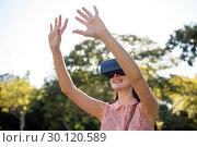 Купить «Smiling woman raising her hands while using a VR headset in the park», фото № 30120589, снято 20 июля 2016 г. (c) Wavebreak Media / Фотобанк Лори