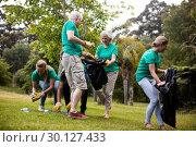Team of volunteers picking up litter. Стоковое фото, агентство Wavebreak Media / Фотобанк Лори