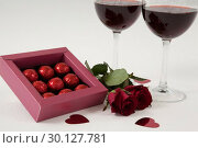 Купить «Bunch of roses, wine glasses and assorted chocolate box», фото № 30127781, снято 8 декабря 2016 г. (c) Wavebreak Media / Фотобанк Лори