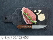 Купить «Sirloin chop, knife and garlic on slate plate», фото № 30129653, снято 20 сентября 2016 г. (c) Wavebreak Media / Фотобанк Лори