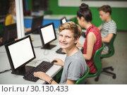 Купить «Portrait of smiling schoolboy studying in computer classroom», фото № 30130433, снято 19 ноября 2016 г. (c) Wavebreak Media / Фотобанк Лори
