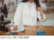 Купить «School girl writing in journal book while experimenting in laboratory», фото № 30130689, снято 19 ноября 2016 г. (c) Wavebreak Media / Фотобанк Лори