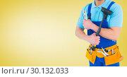 Handy man standing with tools against yellow background. Стоковое фото, агентство Wavebreak Media / Фотобанк Лори