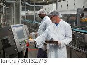 Купить «Two factory engineers operating machine in factory», фото № 30132713, снято 20 октября 2016 г. (c) Wavebreak Media / Фотобанк Лори