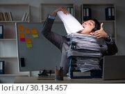 Купить «Young male employee working late at office», фото № 30134457, снято 14 ноября 2018 г. (c) Elnur / Фотобанк Лори