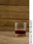 Купить «Glass of whisky on wooden table», фото № 30136637, снято 11 января 2017 г. (c) Wavebreak Media / Фотобанк Лори