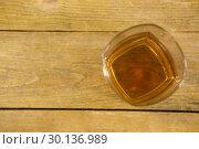 Купить «Glass of whisky on wooden table», фото № 30136989, снято 11 января 2017 г. (c) Wavebreak Media / Фотобанк Лори