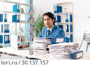 Купить «Young handsome male employee with too much work in the office», фото № 30137157, снято 10 ноября 2018 г. (c) Elnur / Фотобанк Лори