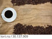 Купить «Coffee cup with coffee beans arranged on sack», фото № 30137909, снято 6 октября 2016 г. (c) Wavebreak Media / Фотобанк Лори