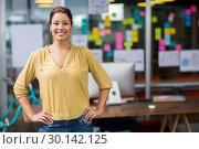Купить «Portrait of smiling female executive standing with hands on hip», фото № 30142125, снято 23 ноября 2016 г. (c) Wavebreak Media / Фотобанк Лори
