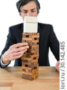 Купить «Businessman arranging building blocks with house model on top», фото № 30142485, снято 24 августа 2016 г. (c) Wavebreak Media / Фотобанк Лори