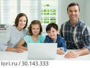 Купить «Portrait of smiling family using laptop in living room», фото № 30143333, снято 29 ноября 2016 г. (c) Wavebreak Media / Фотобанк Лори