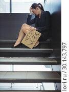 Купить «Depressed businesswoman sitting on stairs holding cardboard sheet with text need work», фото № 30143797, снято 19 ноября 2016 г. (c) Wavebreak Media / Фотобанк Лори
