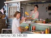 Купить «Smiling waitress giving wrap to customer at counter», фото № 30149381, снято 26 марта 2017 г. (c) Wavebreak Media / Фотобанк Лори