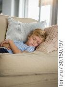 Купить «Boy sleeping on sofa in the living room», фото № 30150197, снято 23 февраля 2019 г. (c) Wavebreak Media / Фотобанк Лори