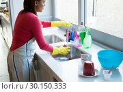 Купить «Woman washing cup in kitchen sink», фото № 30150333, снято 24 марта 2017 г. (c) Wavebreak Media / Фотобанк Лори
