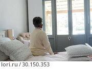 Купить «Senior woman sitting on bed in bedroom», фото № 30150353, снято 24 марта 2017 г. (c) Wavebreak Media / Фотобанк Лори