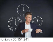 Businessman looking at watch and time clocks in front of blackboard. Стоковое фото, агентство Wavebreak Media / Фотобанк Лори