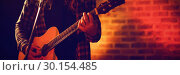Купить «Male singer practicing with guitar in nightclub», фото № 30154485, снято 7 марта 2017 г. (c) Wavebreak Media / Фотобанк Лори