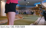 Купить «Playing mini golf. A young woman playing mini golf indoors. Hitting the ball», видеоролик № 30159569, снято 25 марта 2019 г. (c) Константин Шишкин / Фотобанк Лори
