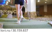 Купить «Playing mini golf. A young woman playing mini golf indoors. Coming closer to the ball», видеоролик № 30159837, снято 25 марта 2019 г. (c) Константин Шишкин / Фотобанк Лори