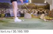 Купить «Playing mini golf. A young woman playing mini golf indoors. Coming closer to the ball, hit it and it gets in the hole», видеоролик № 30160189, снято 25 марта 2019 г. (c) Константин Шишкин / Фотобанк Лори
