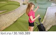 Купить «Playing mini golf. A young blonde woman comes to the bag, taking a golf stick and goes away», видеоролик № 30160389, снято 25 марта 2019 г. (c) Константин Шишкин / Фотобанк Лори